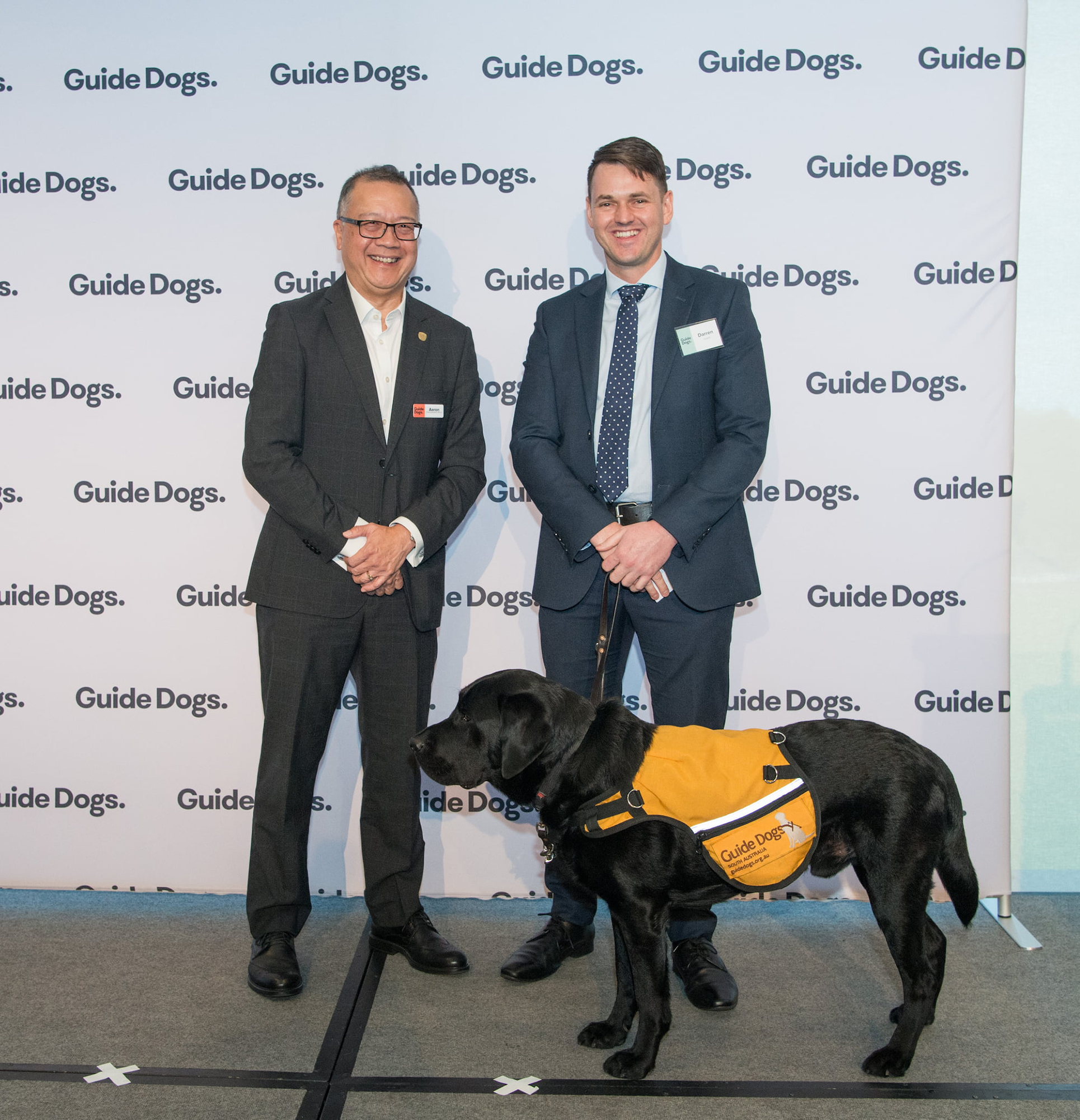 Guide Dogs SA/NT CEO Aaron Chia is standing on stage next to Canine Court Companion Zero, a black Labrador, and his handler Darren.