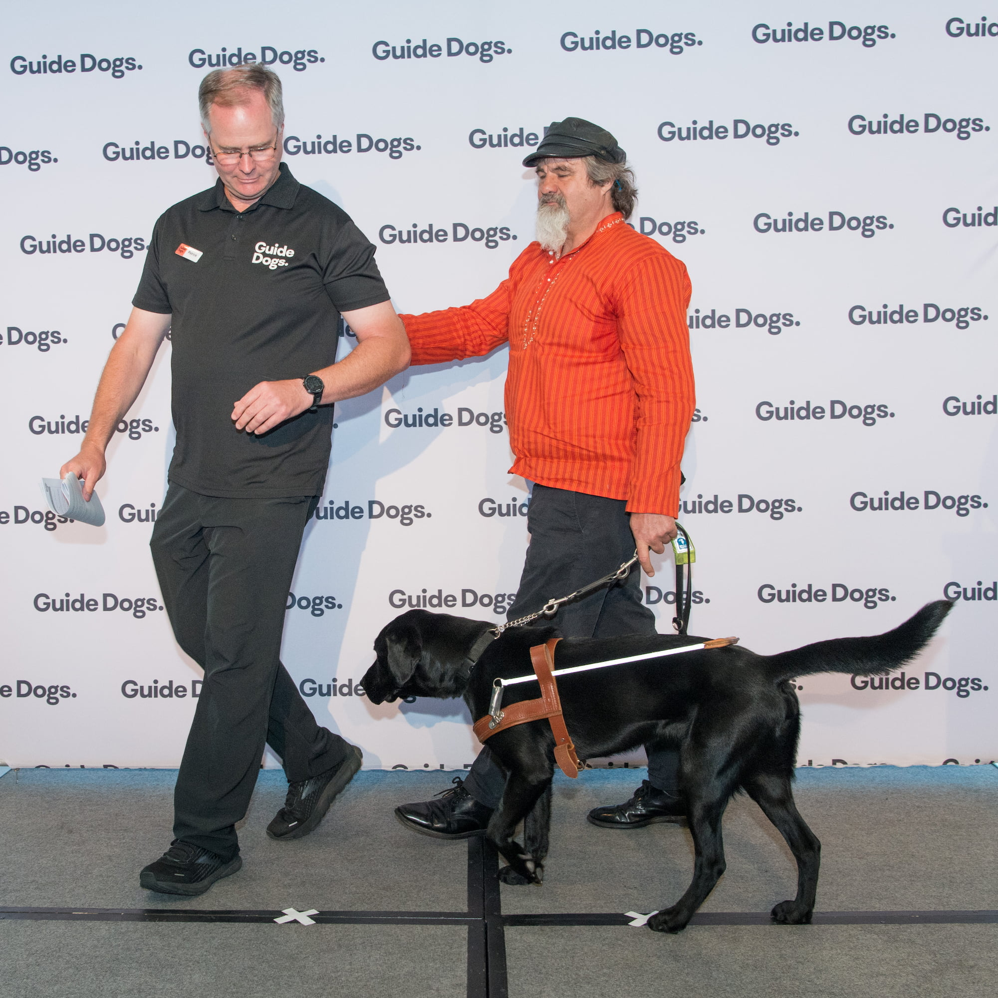 Guide Dogs Client Anthony with his Guide Dog Kit, a black Labrador wearing a harness, being led on stage by a Guide Dogs staff member.