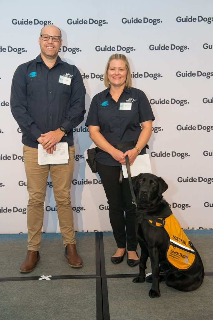 Iris, a black Labrador wearing a yellow Facility Dog jacket, standing on stage with her handlers Paul and Mandy.