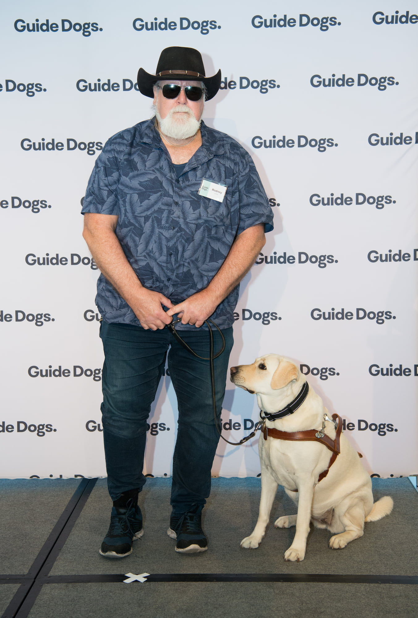 Guide Dogs Client Rodney standing on stage with his Guide Dog Kit, a yellow Labrador wearing a harness.