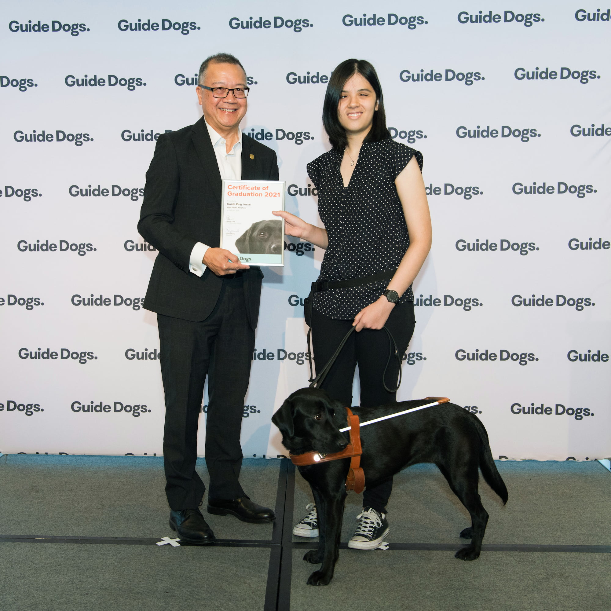 Guide Dogs SA/NT CEO Aaron Chia standing on stage with Guide Dogs Client Sacha and her Guide Dog Jesse, a black Labrador who is wearing a harness. Aaron is presenting Sacha with a certificate.