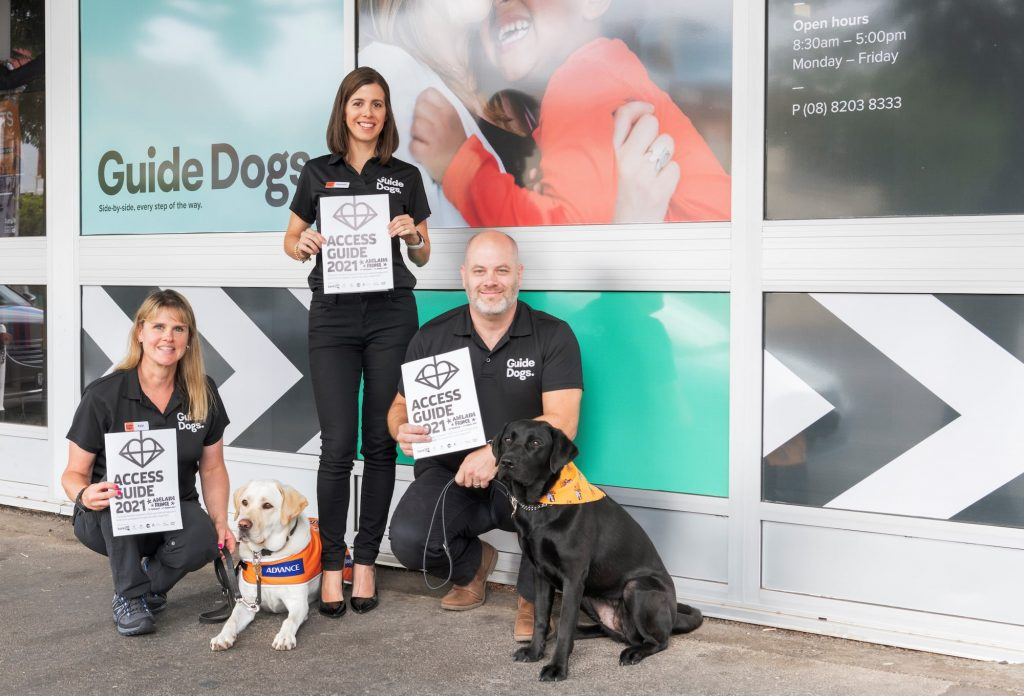 Three Guide Dogs staff members stand outside the Guide Dogs SA/NT building holding the 2021 Adelaide Fringe Access Guide. With them is two Labrador dogs.