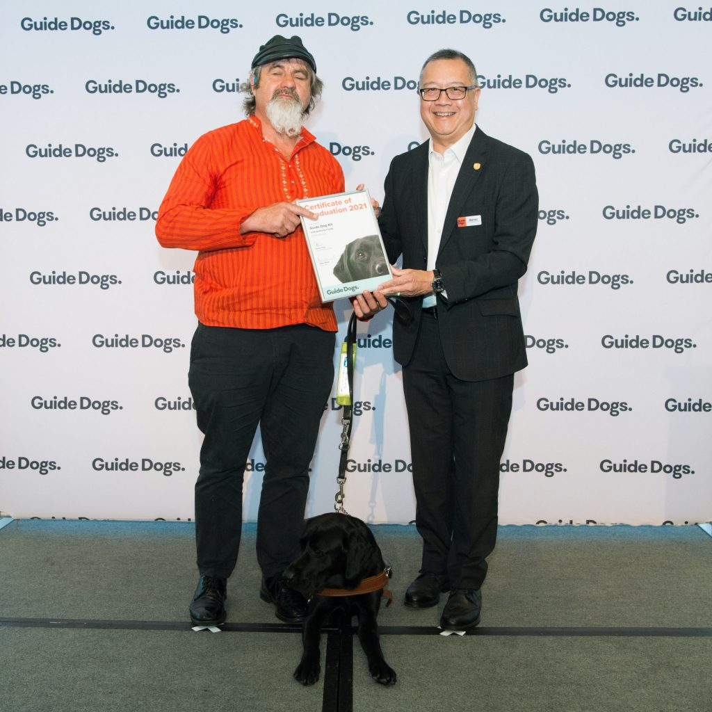 Client Anthony and Guide Dogs SA/NT CEO Aaron Chia standing on stage holding a certificate in front of a Guide Dogs banner. There is a Black Labrador in harness, Kit, sitting between them.